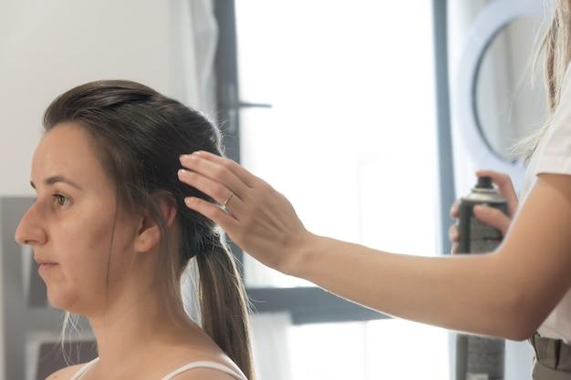 Peluquero rociando laca sobre el cabello del cliente. sesión de peluquería.