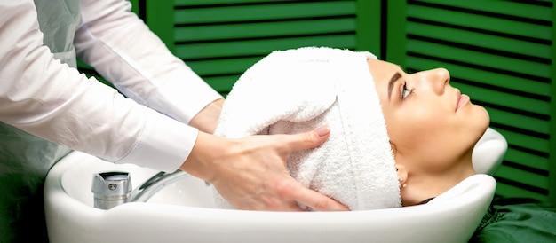 El peluquero seca el cabello del cliente.