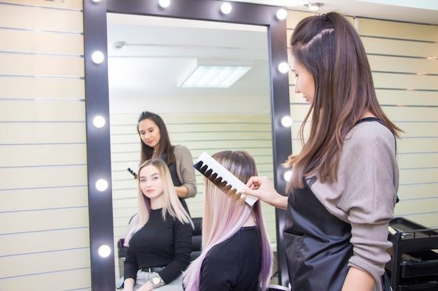 El peluquero selecciona el color del cabello en la paleta del catálogo. coloración del cabello para una niña en un salón de belleza.