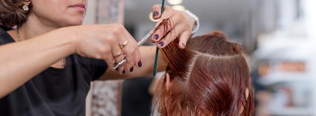 El peluquero sostiene en la mano entre los dedos el mechón de cabello, el peine y las tijeras para cortar el cabello
