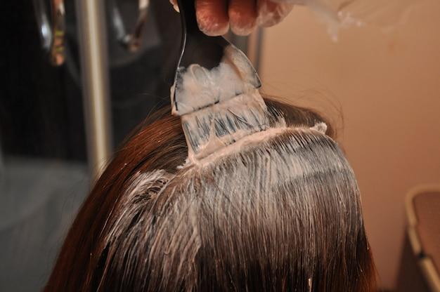 Peluquero teñiendo el cabello de un cliente