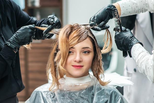 El peluquero se tiñe el cabello femenino.