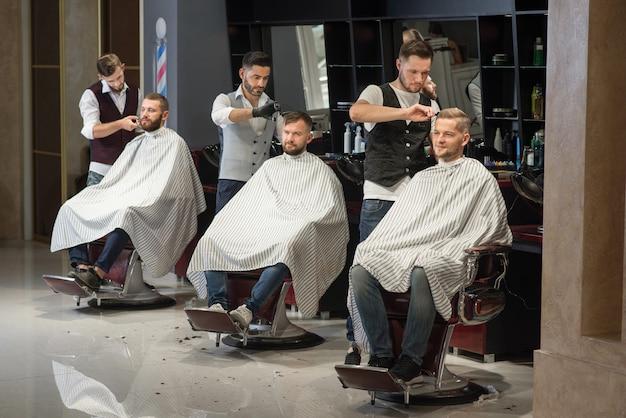Peluqueros arreglando y peinando cortes de cabello de clientes en peluquería.