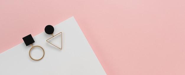Pendientes dorados sobre fondo rosa y blanco