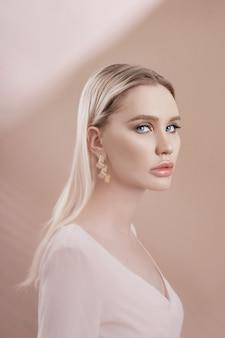 Pendientes y joyas en oreja de una mujer rubia sexy.