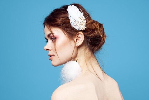 Pendientes mullidos mujer maquillaje brillante vista recortada fondo azul. foto de alta calidad