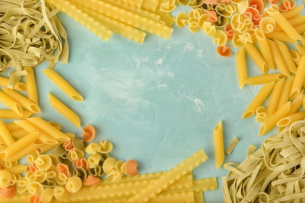 Penne, mafalde, tagliatelle, spaghetti dispuestos en un círculo sobre un fondo azul.