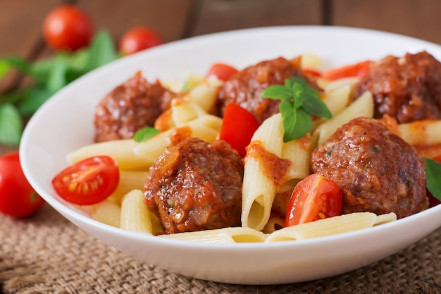 Penne pasta con albóndigas en salsa de tomate en un tazón blanco