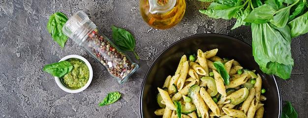 Penne pasta con salsa de pesto, calabacín, guisantes y albahaca. comida italiana. vista superior. endecha plana.