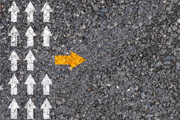 Pensamiento diferente y concepto de disrupción empresarial y tecnológica. flecha amarilla fuera de la dirección de la línea con flecha blanca en el asfalto de la carretera.
