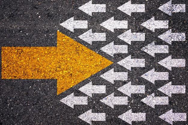 Pensamiento diferente y concepto de disrupción empresarial y tecnológica. flecha amarilla grande en dirección opuesta con flecha blanca sobre asfalto.