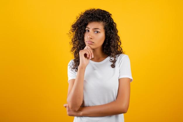 Pensamiento joven de la mujer negra aislado sobre amarillo