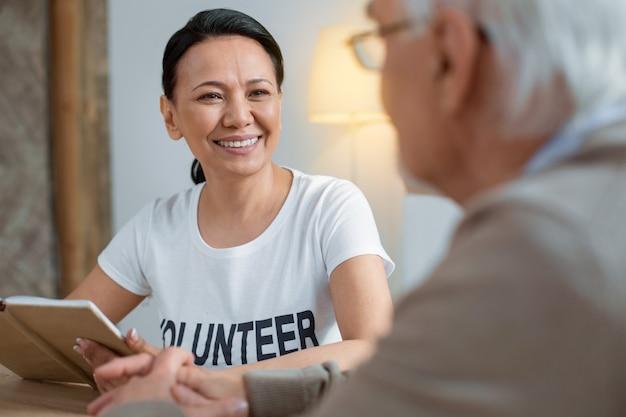 Pensamiento sabio. voluntario alegre alegre sonriendo mientras sostiene el cuaderno y mirando al hombre mayor