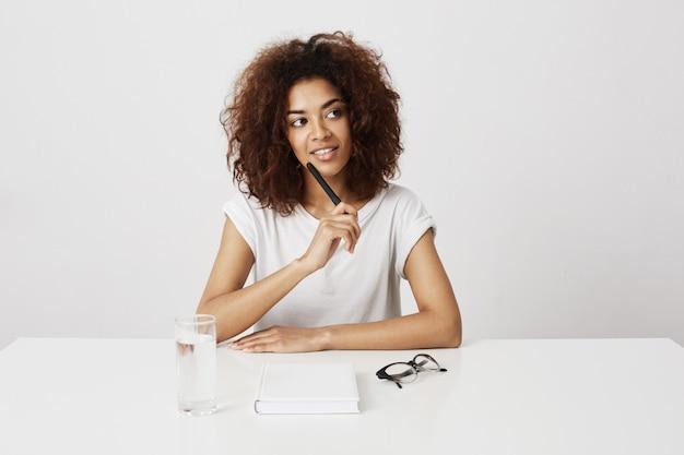 Pensamiento sonriente de la muchacha africana hermosa que se sienta en la tabla sobre la pared blanca. copia espacio