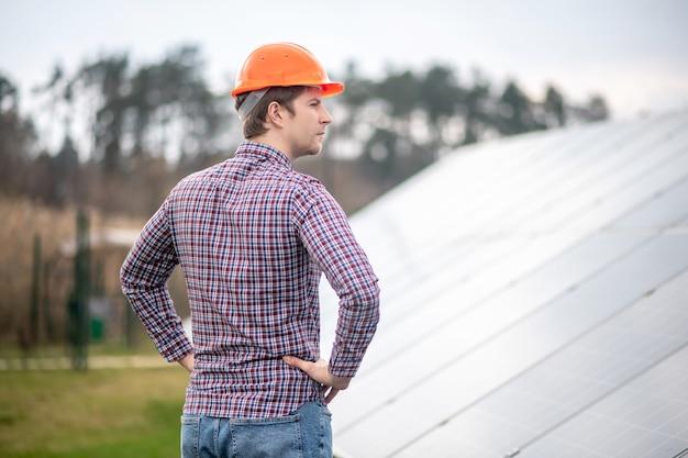 Pensamientos, idea. hombre adulto joven de pensamiento concentrado en casco de seguridad de pie lateralmente cerca de la superficie gris de construcción durante el día al aire libre
