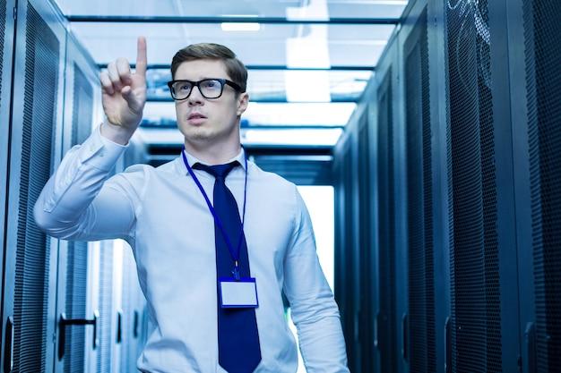 Pensamientos operador serio meditativo de pie cerca de los gabinetes del servidor y apuntando con su dedo