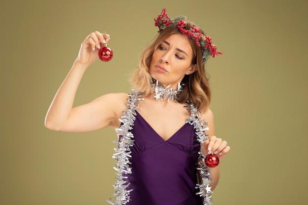Pensando en la hermosa joven con vestido púrpura y corona con guirnalda en el cuello sosteniendo y mirando bolas de árbol de navidad aisladas sobre fondo verde oliva