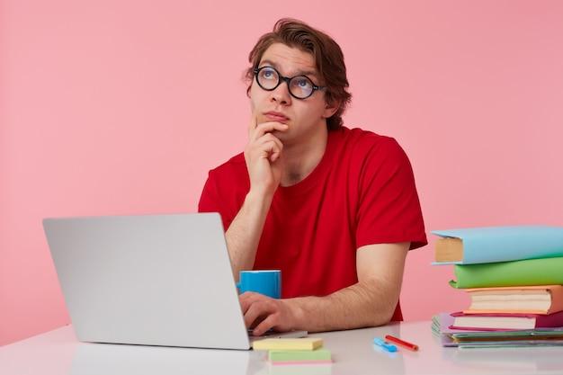 Pensando en el joven estudiante con gafas viste una camiseta roja, el hombre se sienta junto a la mesa y trabaja con la computadora portátil, toca la barbilla, mira hacia arriba y sueña con las vacaciones, aislado sobre fondo rosa.