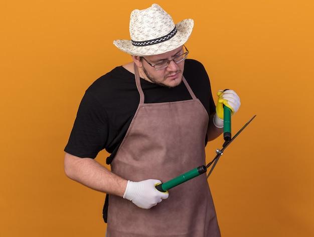 Pensando joven jardinero con sombrero y guantes de jardinería sosteniendo y mirando las tijeras aisladas en la pared naranja