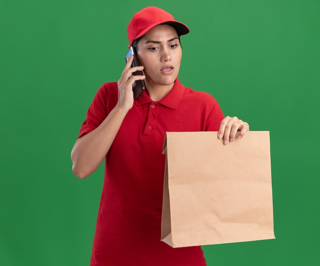 Pensando en la joven repartidora vestida con uniforme y gorra sosteniendo y mirando el paquete de comida de papel habla por teléfono aislado en la pared verde