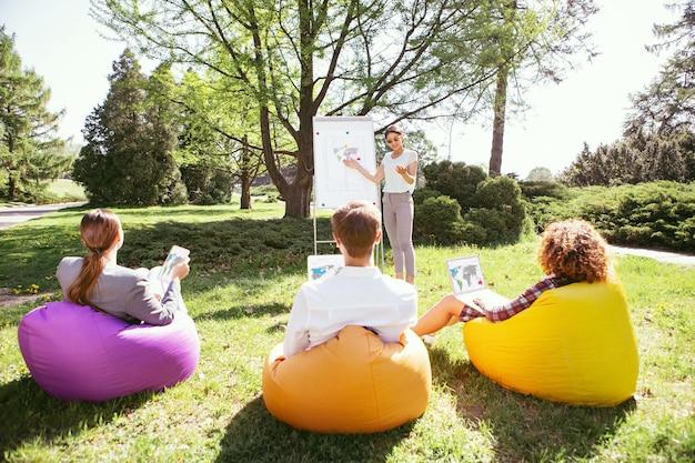 Pensando juntos. alerta a chica elegante de pie en el tablero y discutiendo su proyecto con sus compañeros de grupo