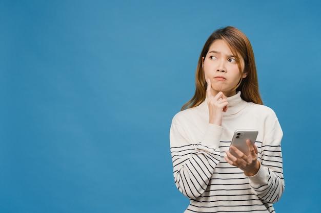 Pensando soñando a la joven dama de asia usando el teléfono con expresión positiva, vestida con ropa casual sintiendo felicidad y parada aislada en la pared azul