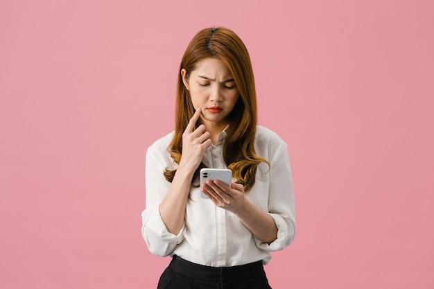 Pensando soñando a la joven dama de asia usando el teléfono con expresión positiva, vestida con ropa casual sintiendo felicidad y parada aislada sobre fondo rosa.