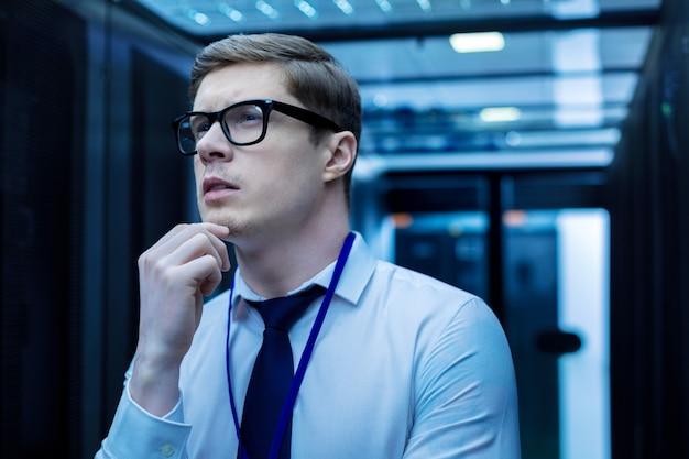 Pensando en el trabajo. trabajador meditativo serio tocando su barbilla y pensando