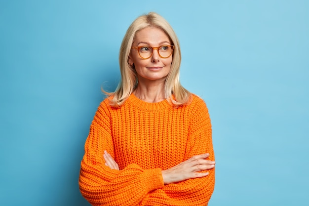 Pensativa adorable rubia de cuarenta años mujer complacida mantiene los brazos cruzados, piensa en algo y mira hacia otro lado lleva gafas suéter de punto.