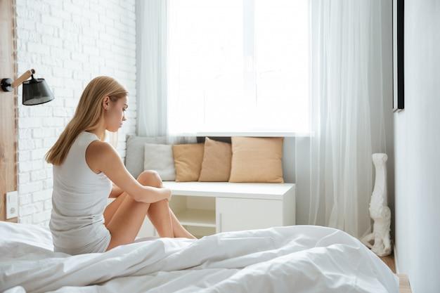 Pensativa deprimida joven sentada y pensando en la cama