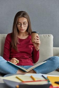 Pensativa diseñadora gráfica de cabello oscuro hace anotaciones en el cuaderno, anota información, mantiene las piernas cruzadas, lleva una taza de café desechable