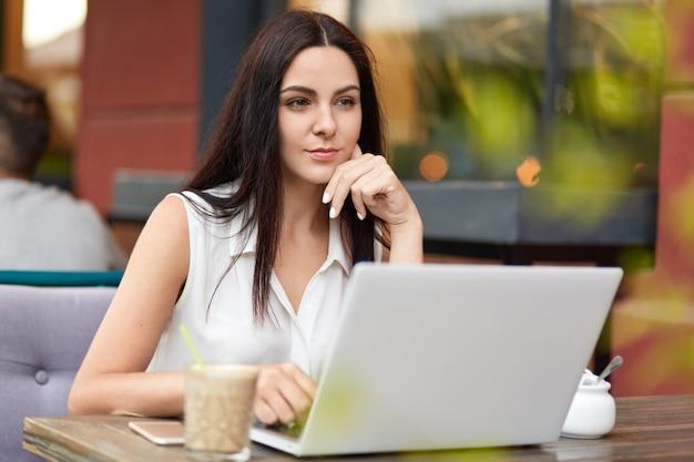 La pensativa editora profesional morena trabaja en la computadora portátil, bebe deliciosas bebidas, usa internet inalámbrico para el trabajo, mira atentamente a la distancia, posa frente a un café al aire libre
