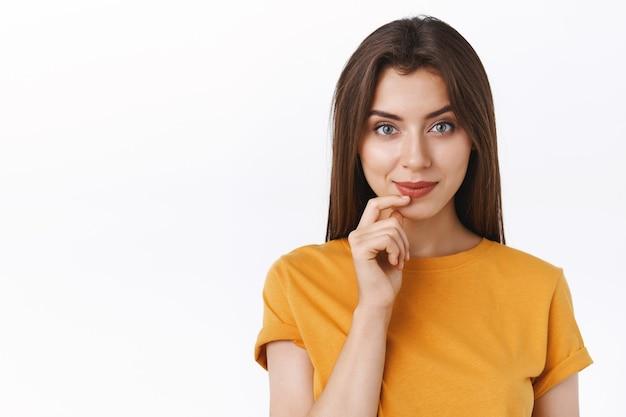 Pensativa, guapa, atrevida, joven y moderna en camiseta amarilla, sonriendo descarada y creativa, tocando el labio tiene una idea interesante, intrigada con la promoción, de pie, pensando en el fondo blanco.