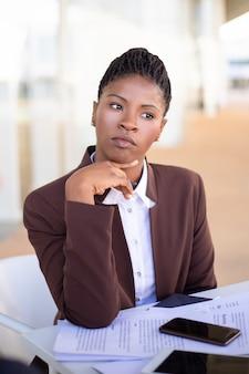 Pensativa joven empresaria pensando en los términos del contrato