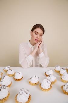 Pensativa joven y guapa mujer sentada a la mesa con pasteles