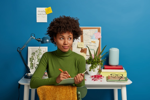 Pensativa joven rizada escribe planes y objetivos futuros en el bloc de notas, piensa en una buena idea