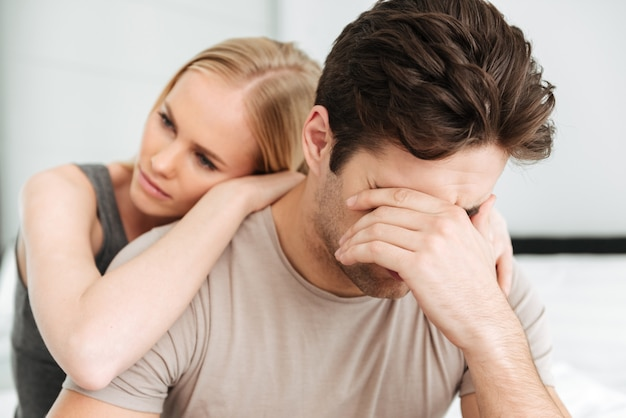Pensativa mujer infeliz consuela a su hombre triste mientras están sentados en la cama