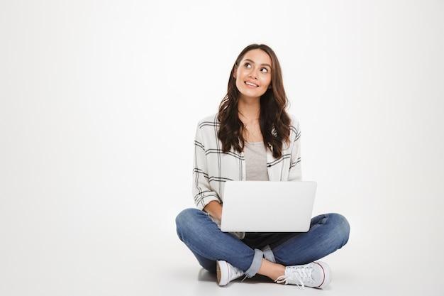 Pensativa mujer morena sonriente en camisa sentada en el suelo con la computadora portátil y mirando hacia arriba sobre gris