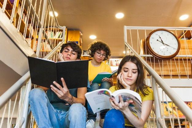 Pensativo adolescentes leyendo en pasos