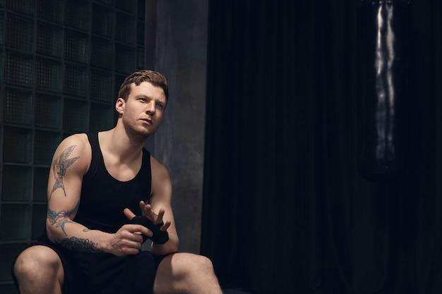 Pensativo atractivo joven europeo vistiendo camiseta sin mangas y pantalones cortos envolviendo vendas de boxeo