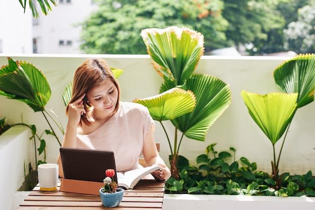 Pensativo bastante joven mujer vietnamita sentada en la mesa de café, tomando café y leyendo un libro interesante