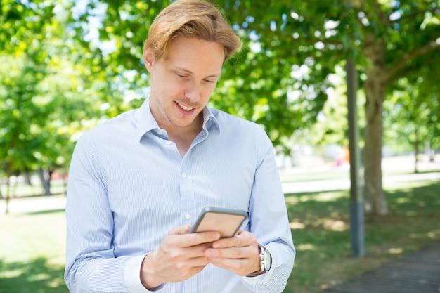 Pensativo chico sonriente mensaje de texto en el teléfono