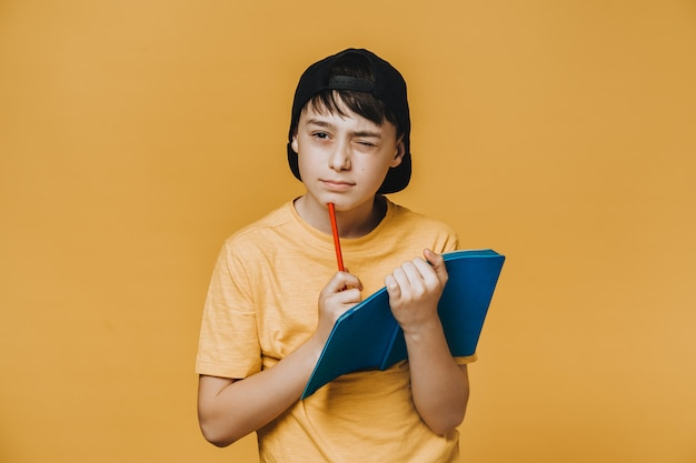 Pensativo colegial vestido con camiseta amarilla y gorra de béisbol negra, sostiene su cuaderno, pensando en la respuesta correcta. concepto de educación y juventud.