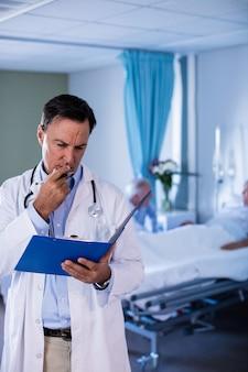 Pensativo doctor hombre mirando informe médico