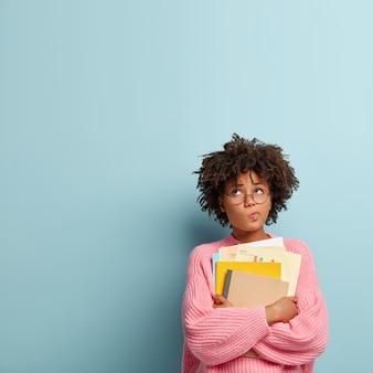 Pensativo estudiante universitario de piel oscura tiene papeles y libros de texto