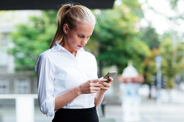 Pensativo joven empresaria sosteniendo el teléfono móvil y escribiendo un mensaje mientras está de pie al aire libre
