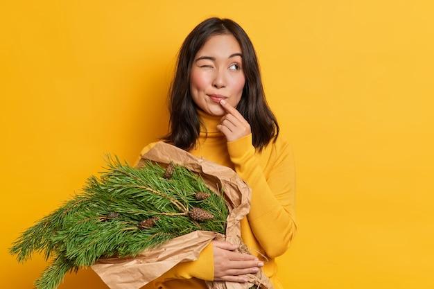 Pensativo joven mujer asiática mantiene un ojo cerrado lleva ramo de ramas spurce con piñas piensa cómo celebrar el año nuevo plantea en interiores