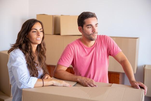 Pensativo joven y mujer de pie entre cajas de cartón en el apartamento, mirando a otro lado