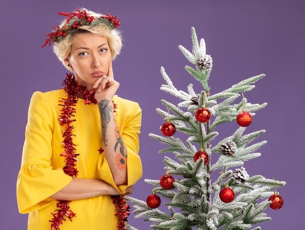 Pensativo joven mujer rubia con corona de navidad y guirnalda de oropel alrededor del cuello de pie cerca del árbol de navidad decorado mirando a la cámara manteniendo la mano en la barbilla aislada sobre fondo púrpura