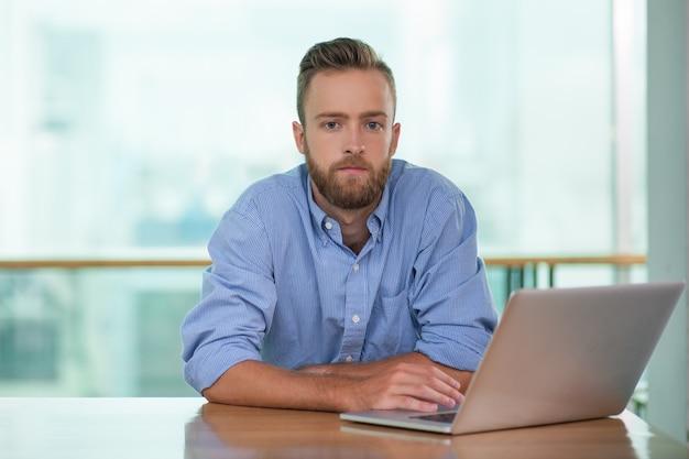 Pensativo joven que trabaja en la computadora portátil en el vector del café
